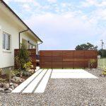 コンクリートの直線的なアプローチの先には、庭と駐車スペースを隔てる高さ160cmのウッドフェンスを施工しています。
